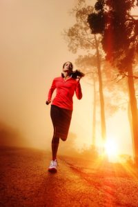 Athlete running on the road in morning sunrise training for marathon and fitness. Healthy active lifestyle latino woman exercising outdoors.