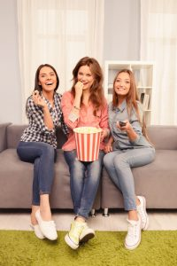 Beautiful girls watching  funny comedy and eating popcorn